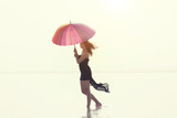 Woman holding colorful umbrella and walking on the salt lake. Sunrise sea and woman with umbrella in hand