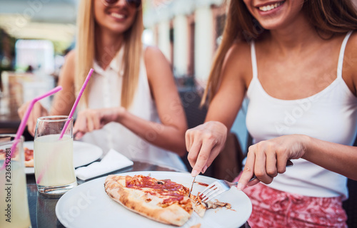 Pizza time. Young girls eating pizza in a cafe. Consumerism, lifestyle