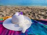 Hat and sunglasses on colorful towel on the beach