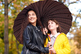 Two girls are together under umbrella in autumn city park. Bright yellow leaves. - 236355963