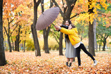 Two girls with umbrella posing in autumn park. Bright yellow leaves and trees. They imitate the wind. - 236356156