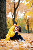 Sad teen girl sits near tree in autumn park. Bright yellow leaves and trees. - 236356315