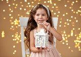 girl child is posing with lantern in christmas lights, yellow background, pink dress - 236356734