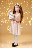 girl child is posing with lantern in christmas lights, yellow background, pink dress - 236356754