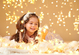 girl child is posing with christmas lights, yellow background, pink dress - 236356793