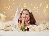 girl child with rose flower is posing in christmas lights, yellow background, pink dress - 236356797
