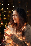 young girl is in christmas lights and decoration, dressed in white, fir tree on dark wooden background, winter holiday concept - 236356911