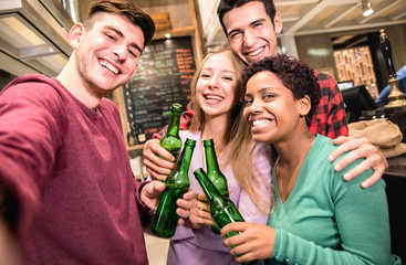 Multiracial friends taking selfie and drinking beer at fancy brewery restaurant - Friendship concept with young people enjoying time together having drunk fun at fashion bar - Focus on middle girl