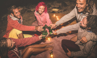 Young hipster friends having fun together at night beach party with campfire light - Friendship travel concept with young people traveler drinking beer at summer surf camping - High iso image