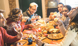 Front view of friends group tasting christmas sweets food and having fun at home drinking champagne sparkling wine - Winter holidays concept with people enjoying time eating together - Warm filter - 236376125