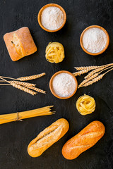 Products made of wheat flour. White flour in bowl, wheat ears, fresh bread and raw pasta on black background top view