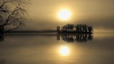 Small island on calm waters of lake. Autumn sunrise time, foggy background, delicate waves. - 236403330