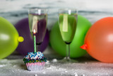 two glasses of champagne and sweet cupcakes on a background of colored balloons - 236409919