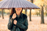 Woman under umbrella posing in autumn park. Bright yellow leaves and trees. - 236413701