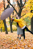 Two girls with umbrella posing in autumn park. Bright yellow leaves and trees. They imitate the wind. - 236413727