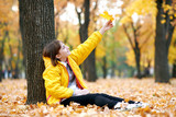 Teen girl sits near tree in autumn park and plays with big maple's leaf. Bright yellow leaves and trees. - 236413911