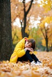 Sad teen girl sits near tree in autumn park. Bright yellow leaves and trees. - 236413946