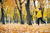 Happy teen girl is running in autumn park with big maple's leaf. Bright yellow leaves and trees. - 236413984