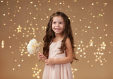 girl child is in christmas lights, yellow background, pink dress - 236414140