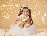 girl child with bear toy is posing in christmas lights, yellow background, pink dress - 236414186
