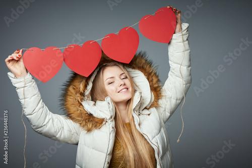 Leinwandbild Motiv Girl in winter coat with hood on holding four hearts garland
