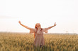 The beautiful girl in the dress is having fun on the field at sunset. Female psychology. The concept of freedom