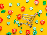 Above view at tomatoes, cucumbers and basil with shopping cart on yellow background - 236454184