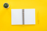 top view of blank spiral notebook and pen on yellow background