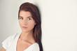 Leinwanddruck Bild - Hübsche junge Frau blickt in die Kamera
