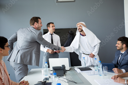 Leinwanddruck Bild Arabian partner handshake with businessman.