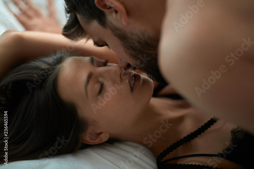 Leinwanddruck Bild passionate lovers man and woman making love in bed.