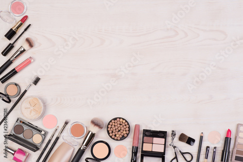 Makeup cosmetics such as eyeshadows, lipstick, mascara and makeup accessories on white, wooden background, top view with copy space - 236467181