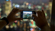 Unidentified man taking a photo of Tokyo skyline with his smart phone from Tokyo Tower, Japan