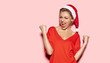 Portrait of happy and excited young girl looking stylish in christmas festive outfit. Holiday and xmas concept. Cheerful model in good mood indoors on pink background