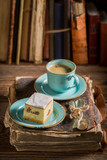 Closeup of rustic cheesecake and coffee on book in library - 236506591