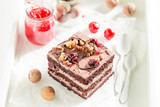 Chocolate cake with walnuts and cherry on white table - 236506702