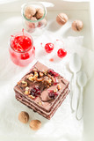 Chocolate cake with cherries and walnuts on white table - 236506713
