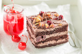 Closeup of sweet chocolate cake with walnuts and cherries - 236506720