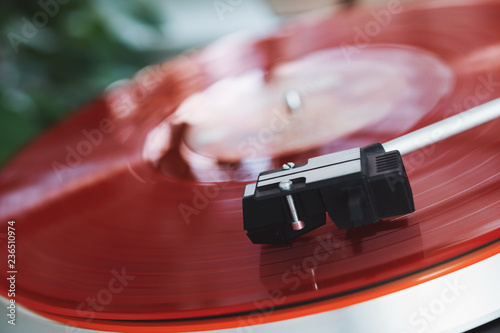 Turntable vinyl record player on a white background. Retro audio equipment for disc jockey. Sound technology for DJ to mix & play music. Red vinyl record and needle. Indoor green plant in a white pot - 236510974
