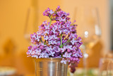 Lilac flowers as spring bouquet in a metal cup on a table setting with wine glasses in the background. Warm shades in a cozy interior. Slight blur for dreamy effect. - 236514757