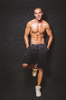 Handsome shirtless fitness man smiling and posing against dark gray background