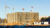 Construction of a new multi-storey building surrounded by forests. Construction cranes against the blue sky. - 236529148