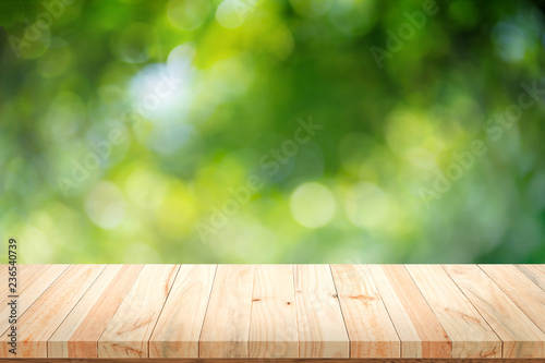 Wooden table on green bokeh background.
