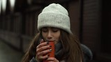 Close portrait of a pretty teenage girl drinking a warm drink from a thermos-mug in snowy evening. - 236543363