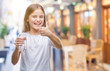 Leinwandbild Motiv Young beautiful girl drinking glass of water over isolated background happy with big smile doing ok sign, thumb up with fingers, excellent sign