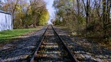 Drone slowly flying above railroad tracks, storage building next to the tracks, trees in autumn foliage on both sides of the tracks, forward-moving dolly shot - 236545319