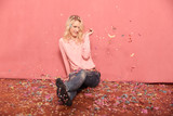 one young smiling woman portrait, looking to camera, sitting on floor surrounded with falling confetti, 20-29 years old, long blond hair. Shot in studio on pink background. - 236547920