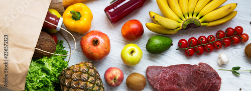 Paper bag of groceries on white wooden background, overhead view. Health food. Healthy eating.