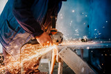 Metalworker cutting iron and metal with a rotary angle grinder and working, generating metal sparks - 236572728