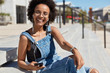 Glad black relaxed young woman listens favourite music or radio broadcasting, looks positively at camera, laughs happily, wears casual clothes, transparent glasses, models outdoor at street.